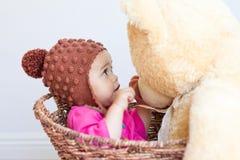 El bebé mira la cara del oso de peluche Imagenes de archivo