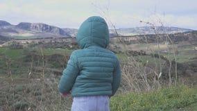 El bebé mira el paisaje de la montaña en España Está jugando en las montañas metrajes