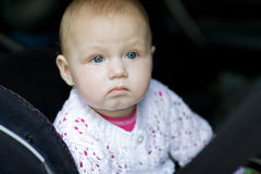 El bebé monta en el coche, sujetado en un asiento del niño fotos de archivo