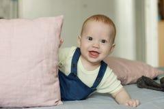 El bebé muy curioso mira fijamente mientras que juega con las almohadas fotos de archivo