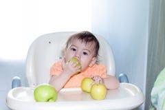 El bebé que come las frutas se sienta en la tabla Fotografía de archivo