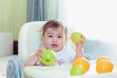 El bebé que come las frutas se sienta en la tabla Fotos de archivo libres de regalías
