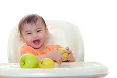 El bebé que come las frutas se sienta en la tabla Foto de archivo libre de regalías