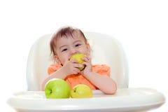El bebé que come las frutas se sienta en la tabla Foto de archivo