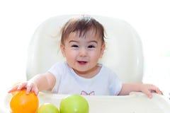El bebé que come las frutas se sienta en la tabla Fotos de archivo
