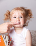 El bebé que conseguía sus dientes limpió con el cepillo de dientes del finger Fotografía de archivo