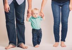 El bebé que lleva a cabo a padres da los ojos anchos Imagenes de archivo