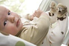 El bebé que miente encendido mueve hacia atrás con los pies para arriba en el aire Fotos de archivo libres de regalías