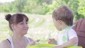 El bebé que se sienta en la madre alimenta la tabla secundaria con una cuchara almacen de video