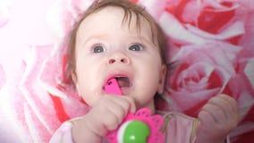El bebé rasguña el juguete de las gomas oh y se divierte almacen de metraje de vídeo