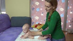 El bebé recién nacido del masaje cuidadoso de la madre en pañales apoya en el sofá 4K almacen de metraje de vídeo