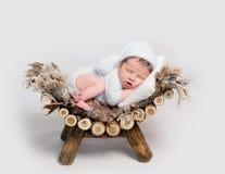 El bebé recién nacido dormido en el vientre se encrespó para arriba en el pesebre foto de archivo libre de regalías