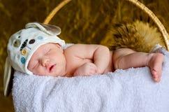 El bebé recién nacido duerme en un sombrero con los oídos Fotos de archivo