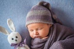 El bebé recién nacido durmiente minúsculo cubierto con púrpura rica coloreó el abrigo imagenes de archivo