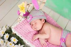 El bebé recién nacido en una liebre hecha punto viste dormir en un abedul de madera del pesebre Imágenes de archivo libres de regalías