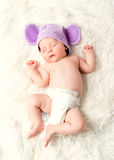 El bebé recién nacido lindo duerme en un sombrero con los oídos foto de archivo