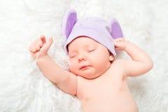 El bebé recién nacido lindo duerme en un sombrero con los oídos imágenes de archivo libres de regalías