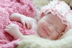 El bebé recién nacido que sonríe en un sueño, bebé recién nacido es sueño foto de archivo libre de regalías