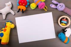 El bebé relleno juega en fondo de madera con la hoja del papel en blanco Fotos de archivo