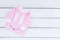 El bebé rosado viste para la niña en el espacio de madera blanco de la copia de la opinión superior del fondo Fotos de archivo libres de regalías