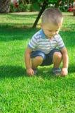El bebé rubio caucásico lindo con el niño de los ojos azules de 2 años se sienta en las caderas en hierba verde Imagen de archivo