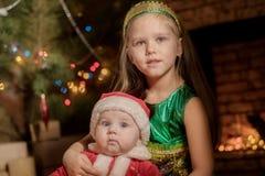 El bebé Santa Claus con la niña celebra la Navidad Imagenes de archivo
