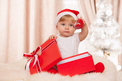 El bebé santa sostiene una caja de regalo roja grande Foto de archivo