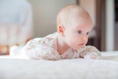 El bebé se arrastra en la cama blanca imagen de archivo