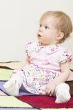 El bebé se está sentando en la tela escocesa hecha punto. Imágenes de archivo libres de regalías