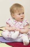 El bebé se está sentando en la tela escocesa hecha punto. Fotografía de archivo libre de regalías