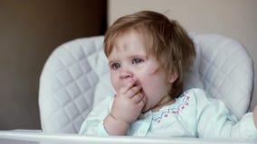 El bebé se sienta en alta silla suave que muerde un cierre de la cápsula para arriba en la cámara lenta metrajes