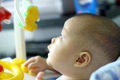 El bebé se sienta en caminante del bebé y la mirada para arriba para el reloj algo Imagenes de archivo