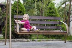 El bebé se sienta en el oscilación en parque Fotos de archivo