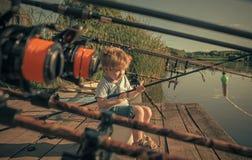 El bebé se sienta en el embarcadero del río con la caña de pescar y la pesca Fotos de archivo