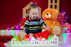 El bebé se sienta en fondo de una guirnalda de luces, los osos de peluche y las casas y los juegos del juguete Fotografía de archivo libre de regalías