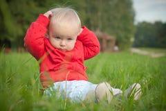 El bebé se sienta en hierba verde en parque Fotografía de archivo libre de regalías