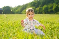 El bebé se sienta en la hierba Fotografía de archivo
