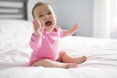 El bebé se sienta en la hoja blanca en el dormitorio foto de archivo libre de regalías