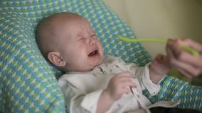 El bebé se sienta en la silla del ` s de los niños La mamá alimenta al niño con la cuchara por primera vez Primer almacen de video