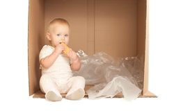 El bebé se sienta en rectángulo y come la galleta Imágenes de archivo libres de regalías