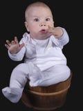 El bebé se sienta en un compartimiento de madera Fotografía de archivo libre de regalías