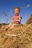 El bebé se sienta en un hayrick Foto de archivo