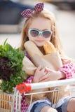 El bebé se sienta en una cesta con la comida cerca del centro comercial Imágenes de archivo libres de regalías