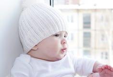 El bebé se sienta en una ventana que pasa por alto la casa siguiente Foto de archivo libre de regalías