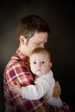 El bebé se sostuvo por el padre imagen de archivo