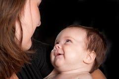 El bebé sonríe en la madre Foto de archivo libre de regalías