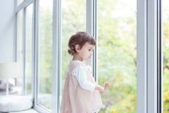 El bebé sonríe en un cuarto cerca de la ventana Imagen de archivo