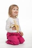 El bebé sonriente está comiendo el plátano maduro Foto de archivo
