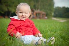 El bebé sonriente se sienta en hierba verde Fotos de archivo
