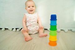 El bebé sonriente se sienta y juega con los juguetes Foto de archivo